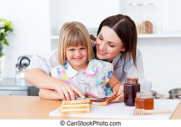 Smiling little girl and her mother preparing toasts