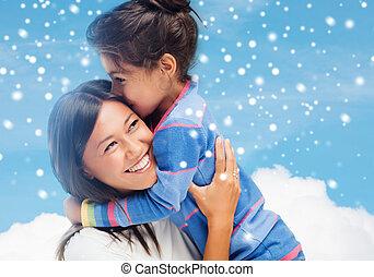 smiling little girl and mother hugging indoors - childhood, ...