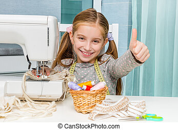 smiling little girl at the table with sewing machine
