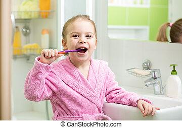 Smiling little girl brushing teeth in bathroom