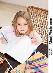 Smiling little girl colouring at the table