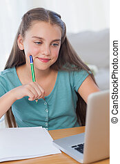 Smiling little girl doing her homework with a computer