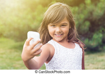 Smiling little girl doing selfie is looking at the camera