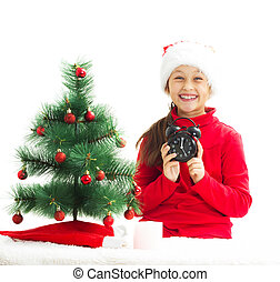 smiling little girl dressed as Santa Claus holding a alarm clock