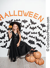 Smiling little girl dressed in halloween costume holding a mask
