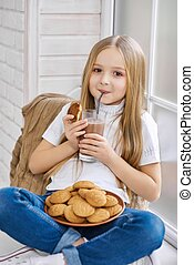 Smiling little girl drinks chocolate milk with cookies.