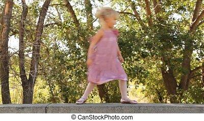 Smiling little girl goes on stone border