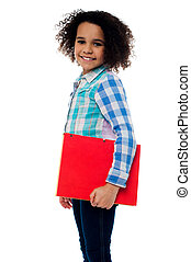 Smiling little girl holding a notebook