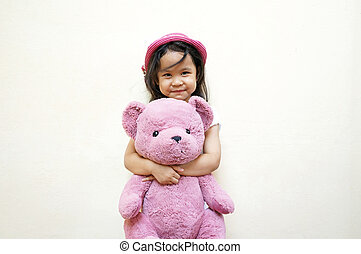 Smiling little girl holding her teddy bear