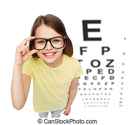 smiling little girl in eyeglasses with eye chart - people,...