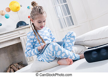 Smiling little girl in pajamas using digital tablet