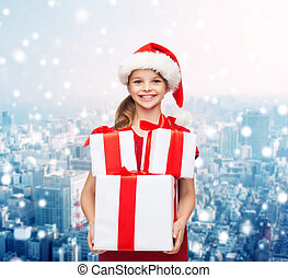 smiling little girl in santa helper hat with gifts - ...