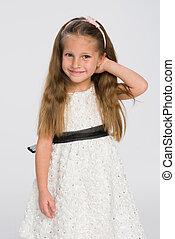 Smiling little girl in the white dress