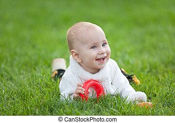 Smiling little girl in white on green grass
