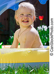 Smiling little girl in yellow pool
