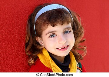 smiling little girl indented front teeth smile on red