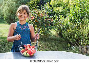 Smiling little girl is a stirring vegetable salad in the garden
