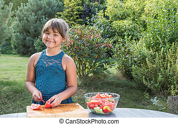 Smiling little girl is cooking in the garden