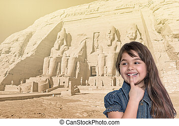 Smiling little girl is standing in front of Abu Simbel temple.