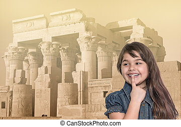 Smiling little girl is standing in front of Kom Ombo temple.