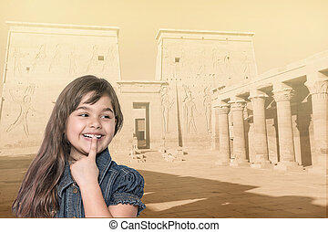Smiling little girl is standing in front of Philae temple.
