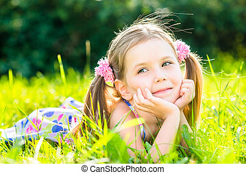 Smiling little girl laying on grass