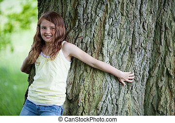 smiling little girl leaning on tall oak in summer