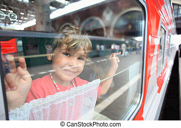 Smiling little girl look from train window