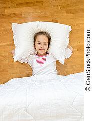 smiling little girl lying on big pillow on floor