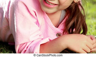 Smiling little girl lying on the grass