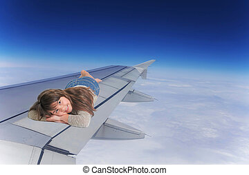Smiling Little girl lying on the wing of an aircraft