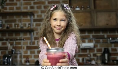 Smiling little girl offering tasty fresh smoothie - Adorable...