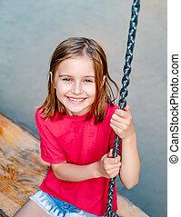 Smiling little girl on park swing