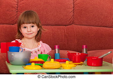 Smiling little girl playing at the table