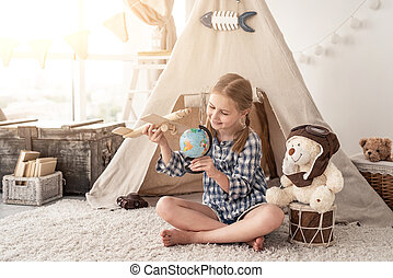 Smiling little girl playing with globe