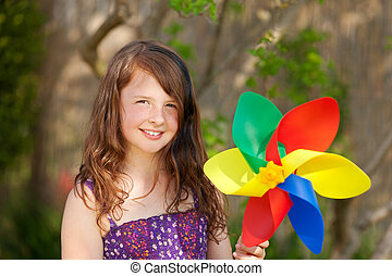 smiling little girl playing with windmill in the garden