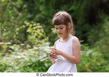 Smiling little girl plays with tablet pc in green park at summer day