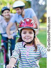 Smiling little girl riding a bike