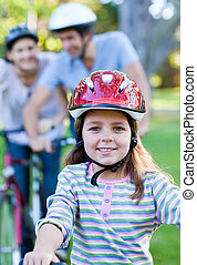 Smiling little girl riding a bike in a park