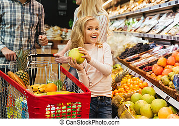 Smiling little girl shopping for groceries