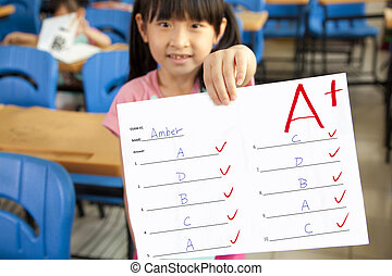 smiling little girl showing exam paper with a plus in the...