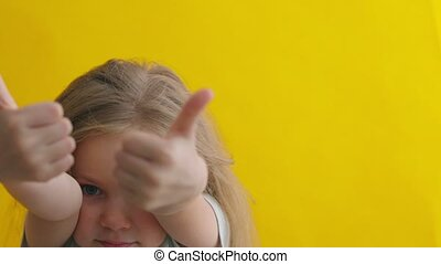 Smiling little girl shows thumbs up gesture over yellow background isolated