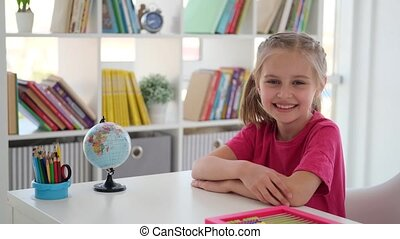 Smiling little girl sitting at school desk in bright classroom