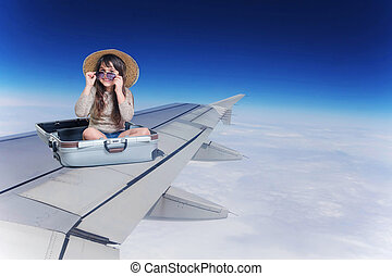 Smiling little girl sitting in suitcase on the wing of an aircraft in flight