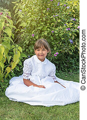 Smiling little girl sitting in white bridesmaid clothes