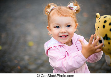 Smiling little girl standing in the autumn park with a yellow black dotted toy in her hands