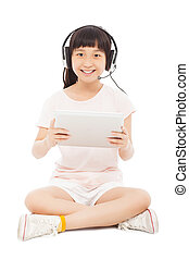 smiling little girl stiiting and holding a tablet with earphone