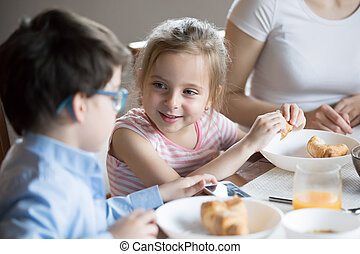 Smiling little girl talking with brother at breakfast at home