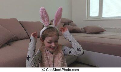 Smiling little girl trying white bunny ears