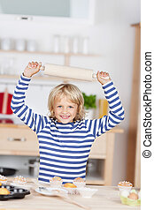 Smiling little girl with a rolling pin